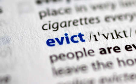 MONTREAL, CANADA - JULY 17, 2019: word evict in a dictionay with meaning. Close-up and selective focus.