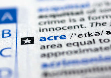 MONTREAL, CANADA - JULY 17, 2019: word acre in a dictionay with meaning. Close-up and selective focus.