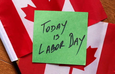 Today is Labor Day written on a green sticky note, the note is lying on Canadian flags 免版税图像