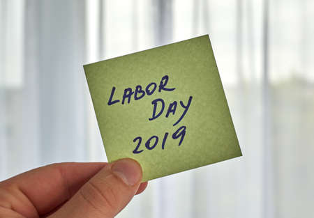 a hand holding Labor Day writing written on a sticky note