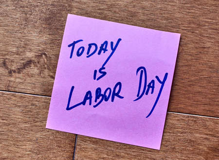 Today is Labor Day written on a sticky note, over a woody background