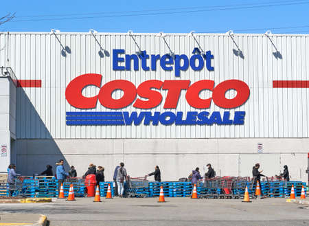 Montreal, Canada - April 4. 2020: People with masks in a line to enter Costco Wholesale. Many stores implemented social distancing which caused lines to enter to the shop due to Coronavirus