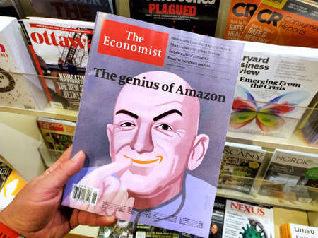 Montreal, Canada - June 30, 2020: The genius of Amazon title and a picture of Jeff Bezos as the Dr Evil on The Economist newspaper in a hand over a stack of magazines. Stockfoto - 150992378
