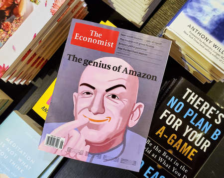 Montreal, Canada - June 30, 2020: The genius of Amazon title and a picture of Jeff Bezos as the Dr Evil on The Economist newspaper over a stack of books.
