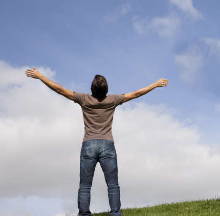Man rising hands with blue sky white clouds. Man stands arms up on the mountain