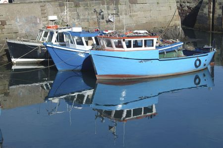 tiedup: reflections of boats tied-up in harbour on calm water