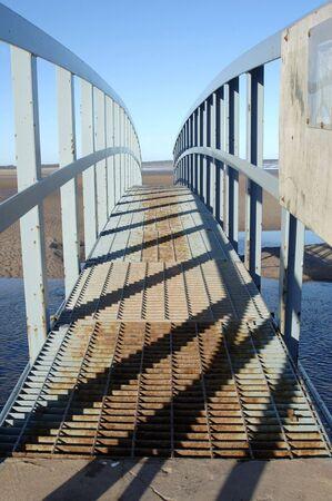 sidelit: steel metal bridge on coast for pedestrians and sidelit casting shadows