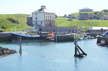 tiedup: view of Eyemouth harbour with fishing boats and Lifeboat with Old Customs House behind
