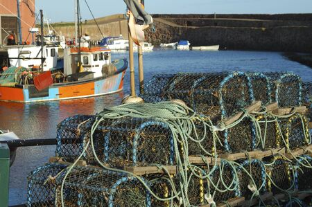lobster pots: looking over lobster pots and trawlers at Dunbar harbour