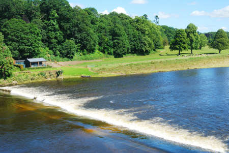 weir: River Tweed weir, meadow and fishing hut near Coldstream from Borders bridge