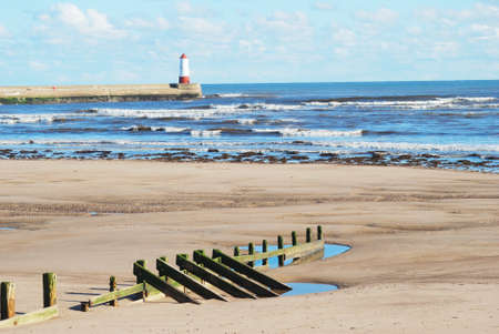seascape of Spittal beach with wooden barrier, sea,waves,sand, with lighthouse