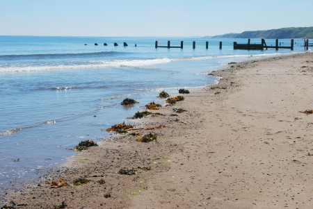 spittal: seascape of Spittal beach with wooden barrier, glistening sea,waves,sand and seaweed  Stock Photo