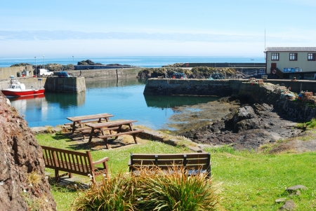 lobster boat: harbour, boat, seats and lifeboat shed at St  Abbs at St  Abbs in Berwickshire
