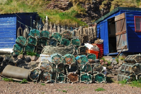 lobster pots: lobster pots, ropes, boxes wooden hut at St. Abbs harbour Stock Photo