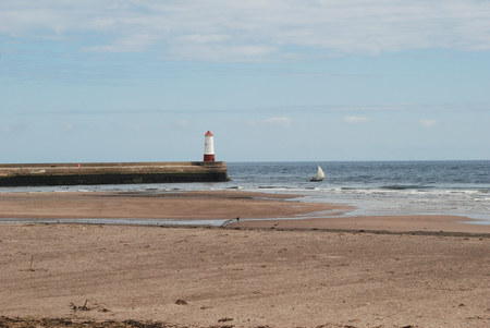 lighthouse, beach and old sailing yacht at Spittal