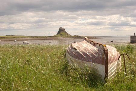 lindisfarne island castle and harbour bay and boats on an overcast day Stock Photo
