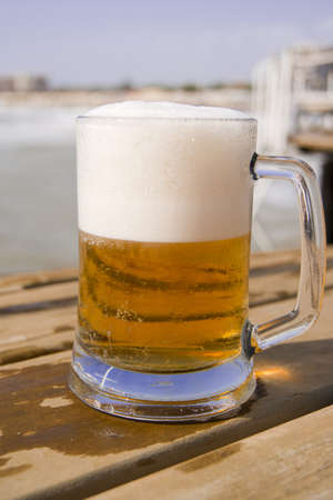 near beer: Mug of beer on the wooden pier near the sea in sunny day