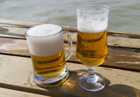 bocal: Mug of beer and bocal of  beer on the wooden pier near the sea in sunny day Stock Photo