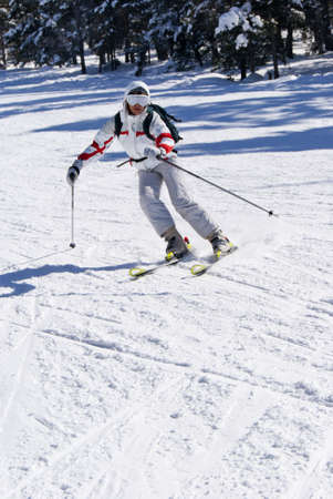 Beautiful skier skiing on the slope in mountain`s forest