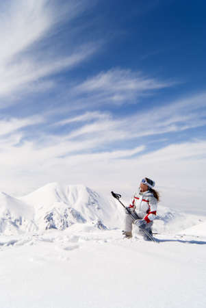 Beautiful skier on the top of mountain looking at the sky photo