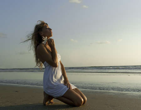Gorgeous woman in white dress kneel on the beach on sunset Stock Photo
