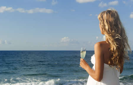 Beautiful woman in white dress looking at the sea