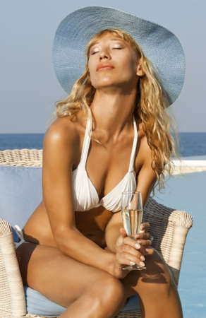 Glamour beautiful woman in white bikini with glass of wine relax near pool on the beach Stock Photo