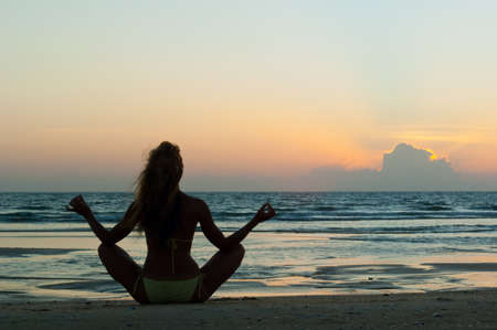 inner peace: Meditating woman on the sand beach at sunset background in India, Goa  Stock Photo