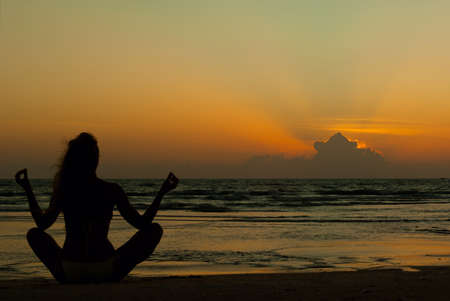 Silhouette of a woman meditating by the sea on sunset photo