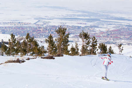 Beautiful skier posing on top of mountain in Palandoken. On the background view of Erzurum, Turkey.