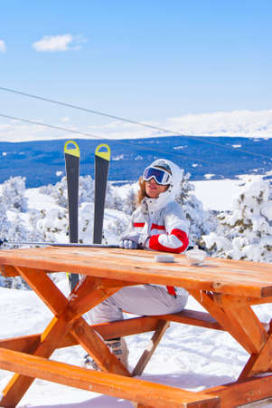 Apres ski in Sarikamis. Beautiful skier waiting for order in cafe on top of mountain. photo