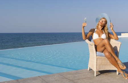 Beautiful woman in white bikini relax in armchair near infinity pool on the beach photo