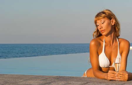 Glamour beautiful woman in white bikini relaxing in infinity pool with glass of wine photo