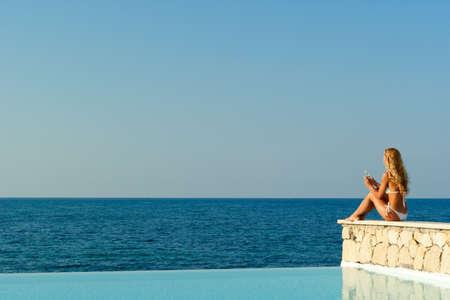 Beautiful woman in white bikini sitting near infinity pool and looking to the sea Stock Photo