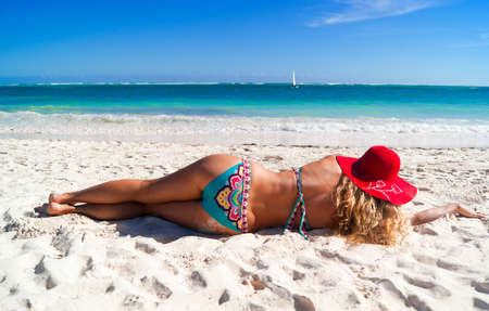 Pretty woman lying on the caribbean beach and looking far