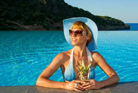 bikini island: Beautiful woman with pineapple in the swimming pool near coast