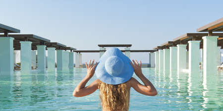 Beautiful blonde woman relaxing near extraordinary pool in sunny day