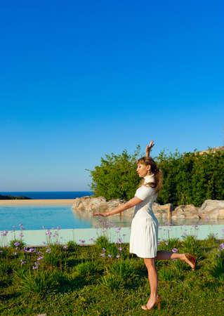 Beautiful woman in white dress meditating near water