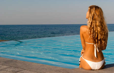 Beautiful woman in white bikini sitting near infinity pool on sunset and looking far