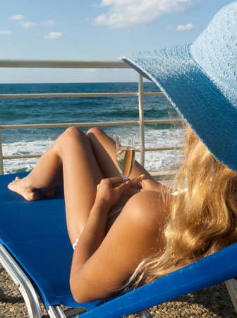 Attractive woman in hat relax on chaise longue near coast photo