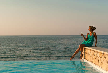 Beautiful woman with glass of wine sitting on the edge of infinity pool