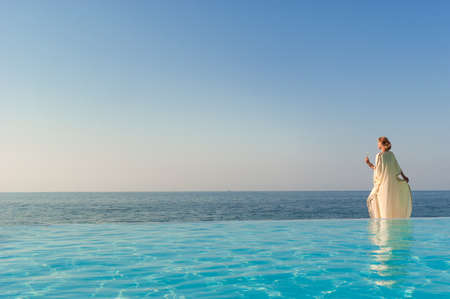 View of antique greek woman near infinity pool on a coast