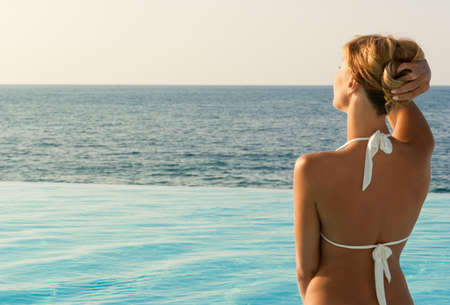 Sexy woman in white bikini near edge of infinity pool looking far on horizon photo