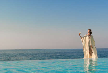 Greek style woman with glass of wine stand on the edge of infinity pool near seaside