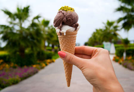 Ice cream cone with two scoops in woman hand