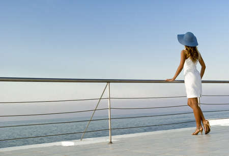 Elegant sexy woman in white dress standing near railings and looking on sunset. Like yacht style. Stock Photo