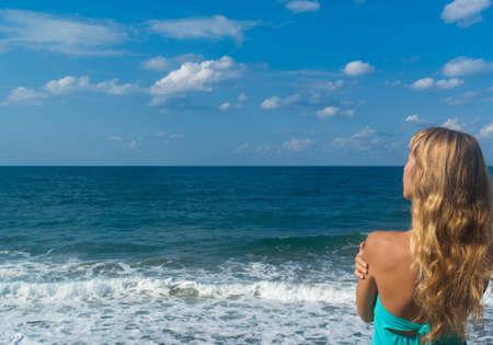 mujer mirando el horizonte: Mujer rubia sexy de pie en una playa y mirar a lo lejos en el horizonte