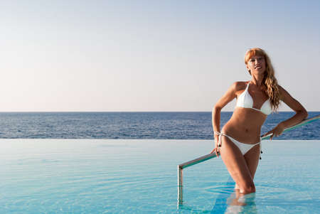Smiling woman in white bikini standing in infinity pool and looking at the camera