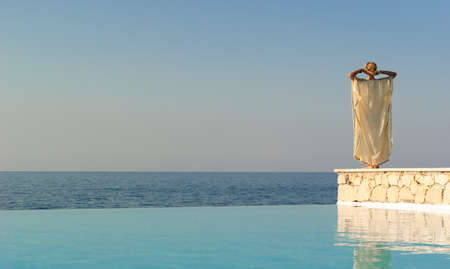 Rear view of greek style woman near infinity pool at sunset