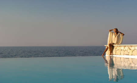 Greek style woman sitting on edge of infinity pool at sunset